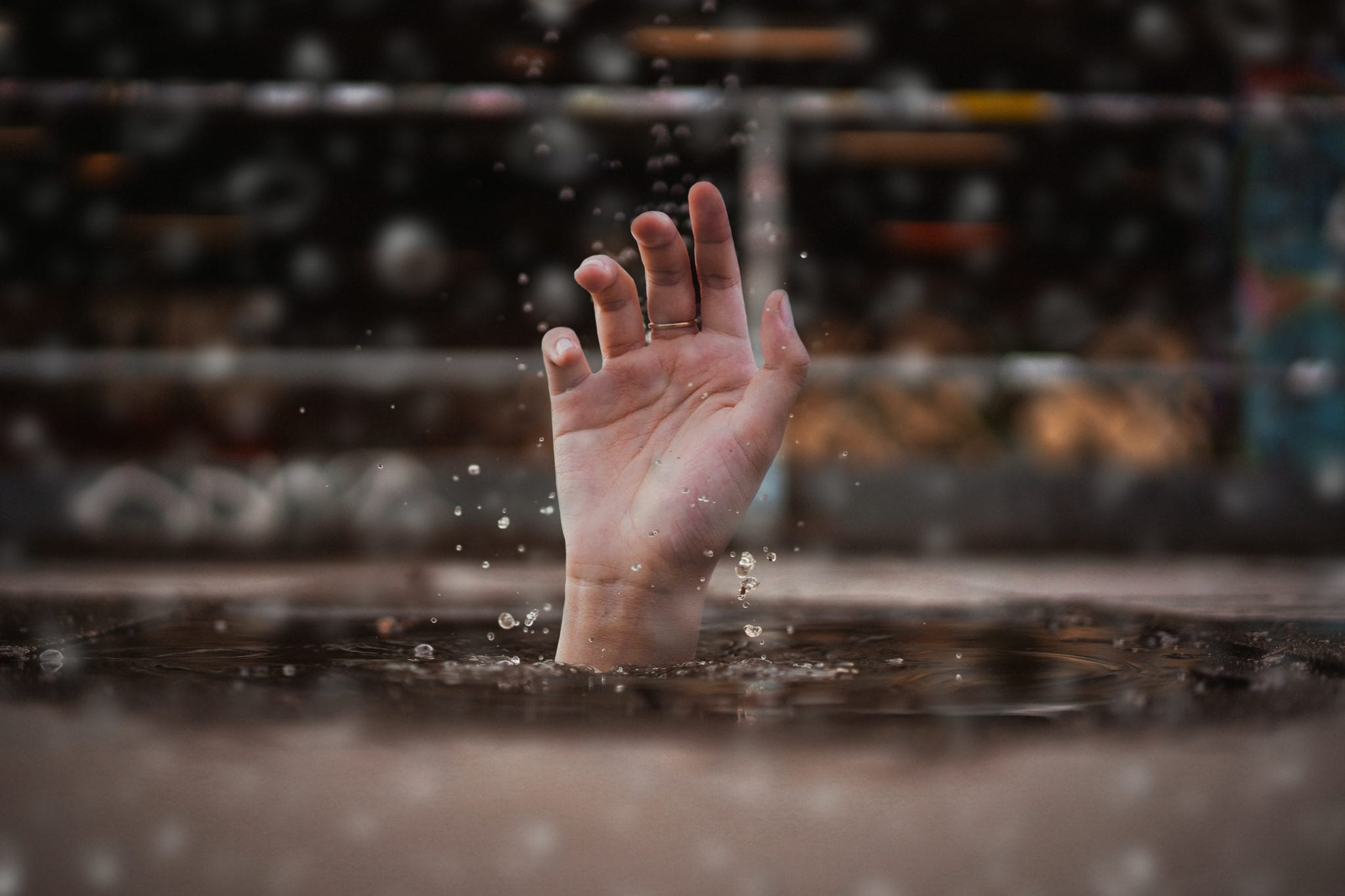 person drowning extending a hand above the water for help
