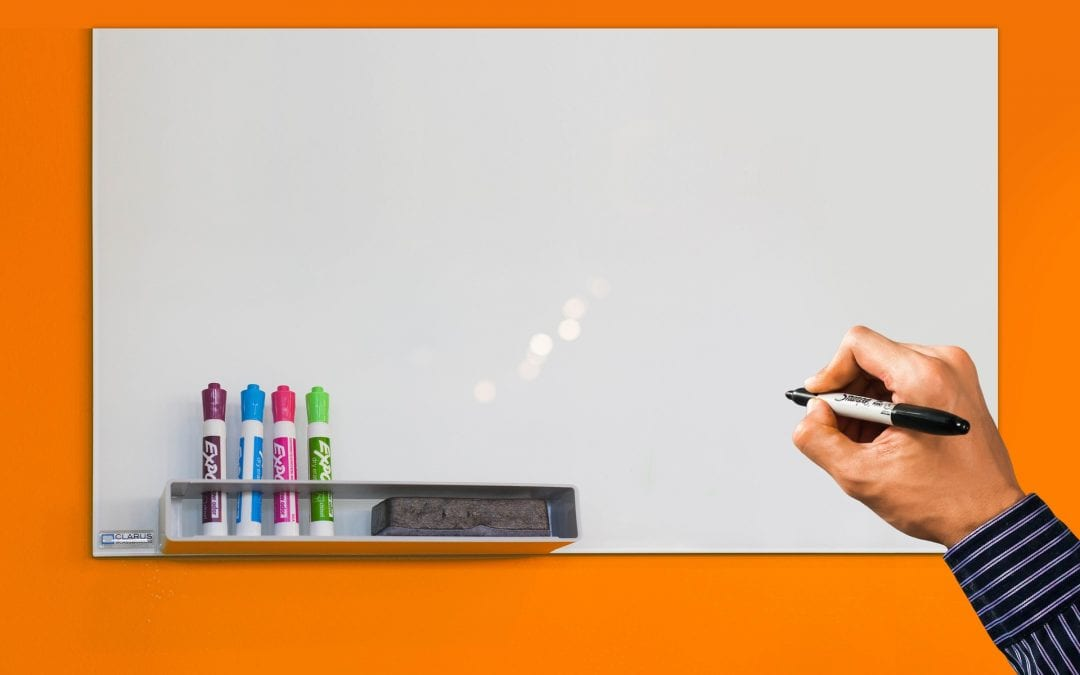a blank whiteboard against an orange wall with a hand prepared to write on it