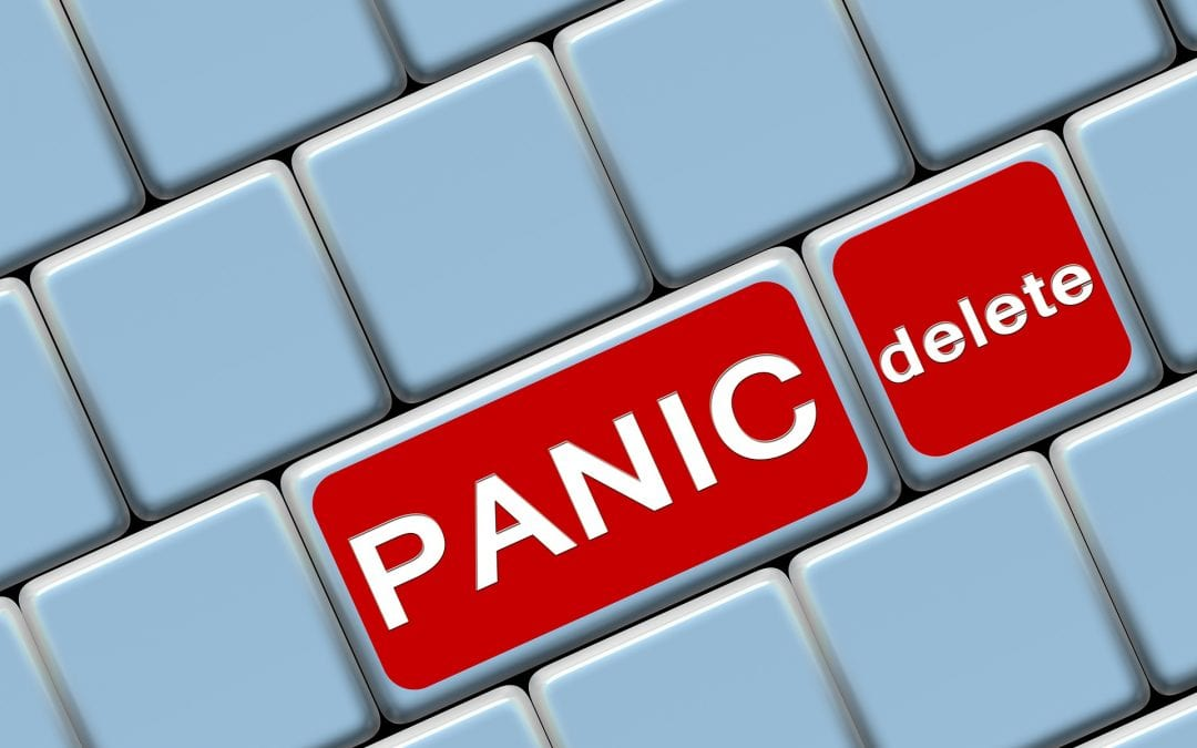 red panic button and red delete button on an all white keyboard