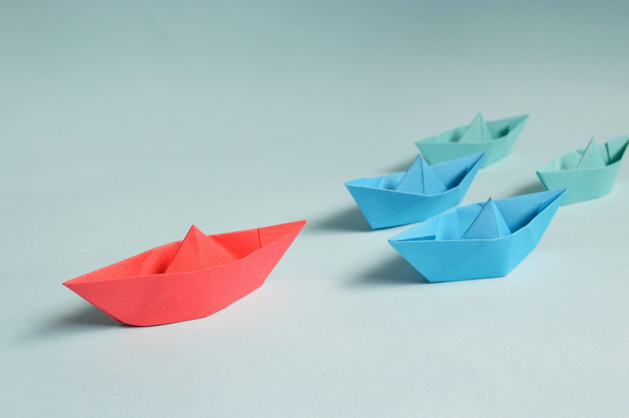 red paper boat leading blue and green paper boats
