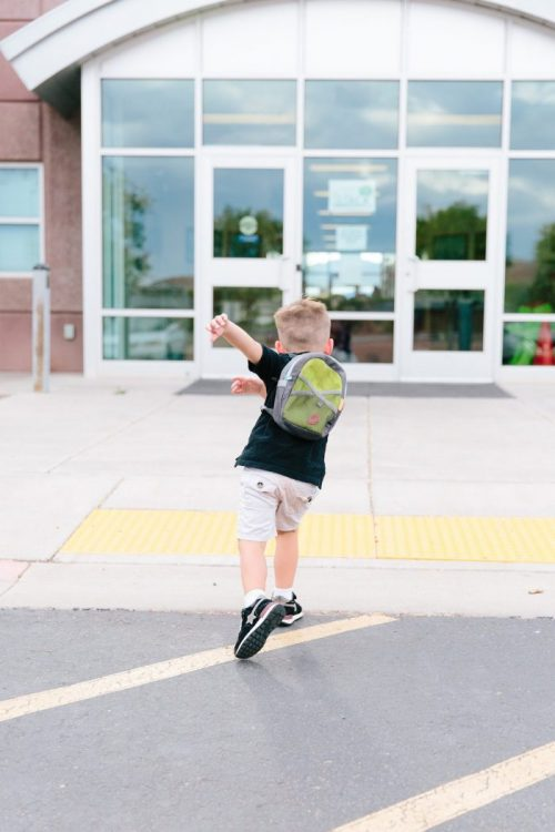 young boy walking excitedly into school